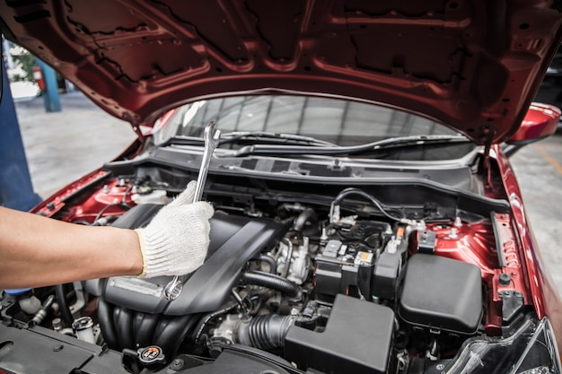 車のサービスとメンテナンスを行う自動車整備士のレンチを親指で押したままにします。