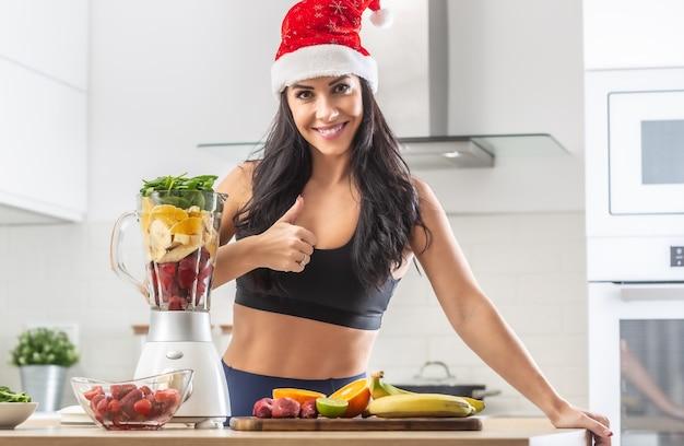 健康的なものでいっぱいの健康的なスムージーメーカーの隣にあるトレーニング服に立っているサンタの帽子をかぶった女性が親指を立てます。