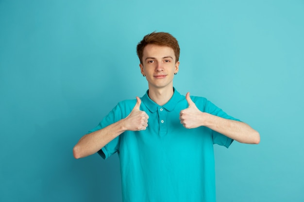 Thumbs up. caucasian young man's modern portrait isolated on blue  wall, monochrome. beautiful male model. concept of human emotions, facial expression, sales, ad, trendy.