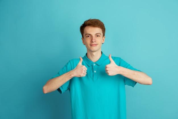 いいぞ。青い壁、モノクロで隔離の白人青年の現代の肖像画。美しい男性モデル。人間の感情、顔の表情、販売、広告、トレンディの概念。