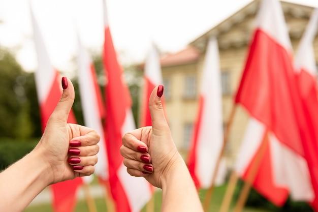 Жест пальца вверх с флагами польши позади