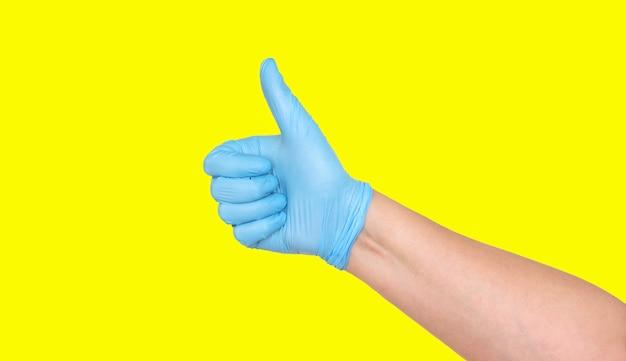 Большие пальцы руки в синей латексной перчатке на желтом фоне.
