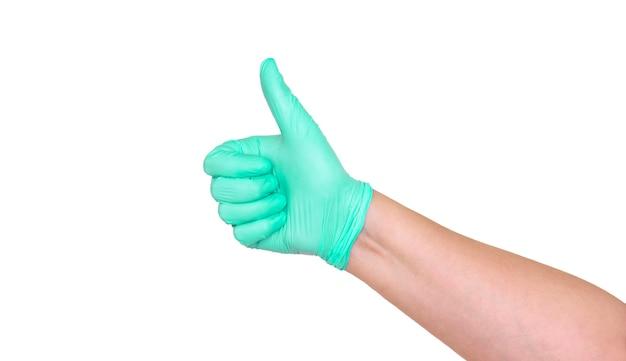 Большие пальцы руки в зеленой латексной перчатке на белом фоне.