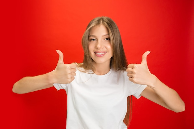 Thumbs up. portrait of young caucasian woman on red studio wall