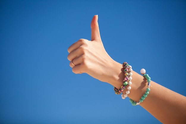 Thumbs up sign on a woman's hand against the turquoise sea