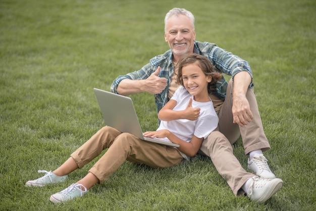 いいぞ。息子と父はラップトップと一緒に座って幸せそうに見えます