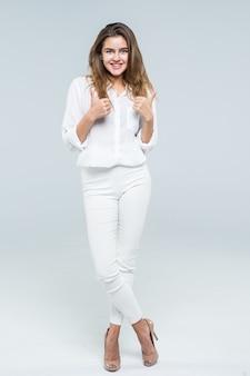 成功女性の幸せな笑顔を親指します。白い背景の上に全身で分離された若い成功した実業家の高角度のビュー。