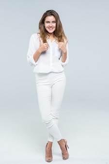 Thumbs up success woman happy smiling. high angle view of young successful businesswoman isolated in full body on white background.