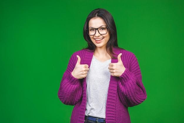 いいぞ。緑の背景に分離された冬の居心地の良いセーターを着ている陽気な美しい少女。