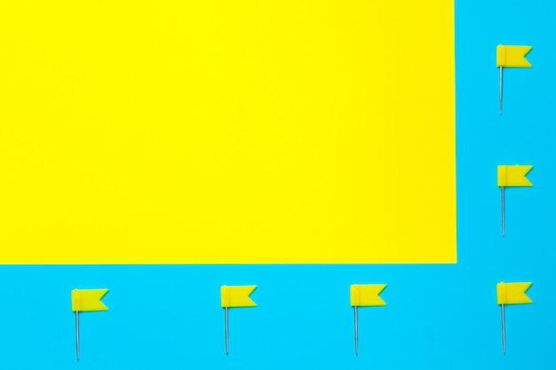 파란색과 노란색 블록에 플래그가있는 압정