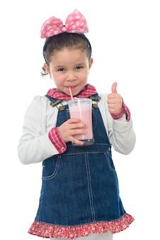 いちごのミルクシェイクを飲む若い女の子を突き上げる