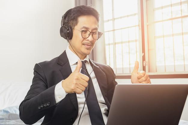Бизнесмен успешный с thumps вверх пока имеющ работу видеоконференции от домашней концепции.