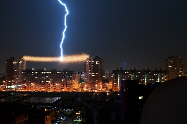 Thunderstorm in the city, lightning struck in the power line between the house