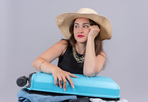 Thunking traveler young girl wearing black undershirt in hat holding open suitcase on white background