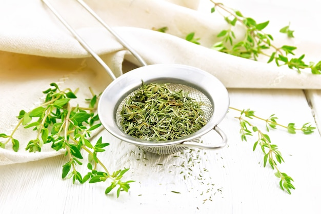 Thyme dry in a metal strainer, fresh greens of grass and linen towel on the background of white wooden board
