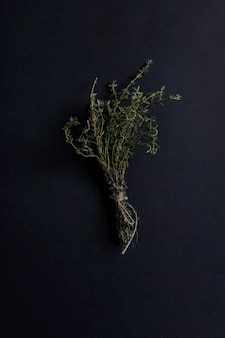 Thyme herb in black table, top view