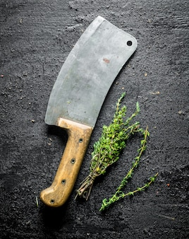 Thyme with a big knife on black rustic table.