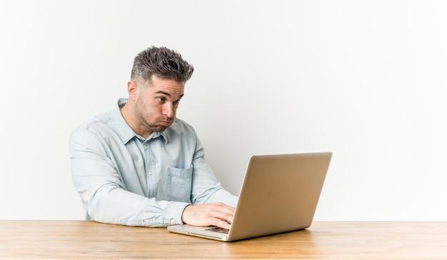 彼のラップトップで働く若いハンサムな男は頬を吹く、tiの表現をしています。表情