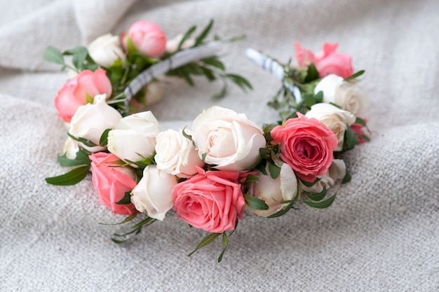 Tiara of artificial roses on wooden .