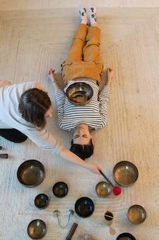 노래 그릇 소녀와 티베트 요법은 휴식을 위해 집에서 청동 접시로 건강한 마사지를받습니다.