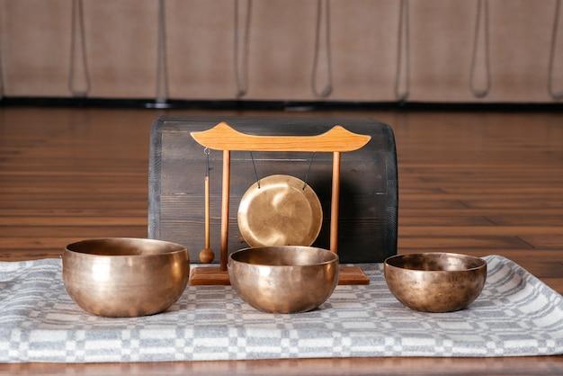 Тибетские поющие чаши ручной работы на полу в классе йоги, концепция звуковой терапии