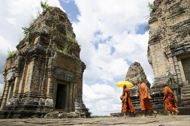 Tibetan monks in orange robes visiting remote cambodian temples to meditate.