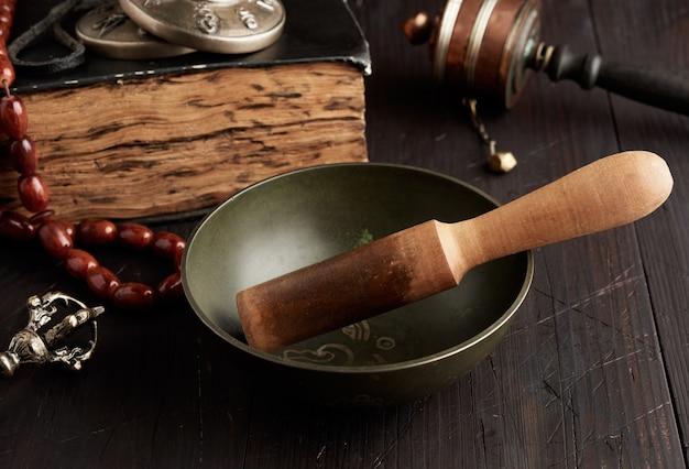 Тибетская поющая медная чаша с деревянной колотушкой на коричневом деревянном столе