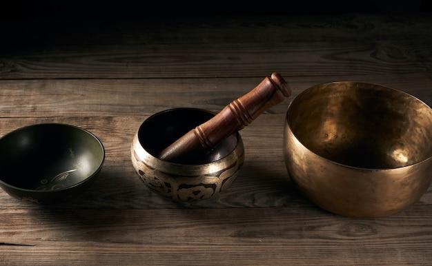 Тибетская поющая медная чаша с деревянной тарелкой на коричневом деревянном столе