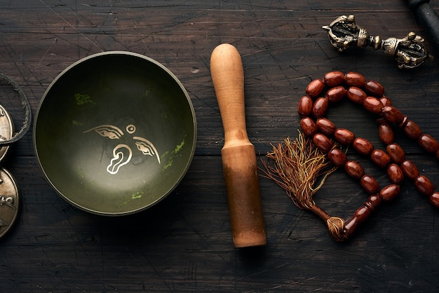 Tibetan singing copper bowl with a wooden clapper on a brown woo
