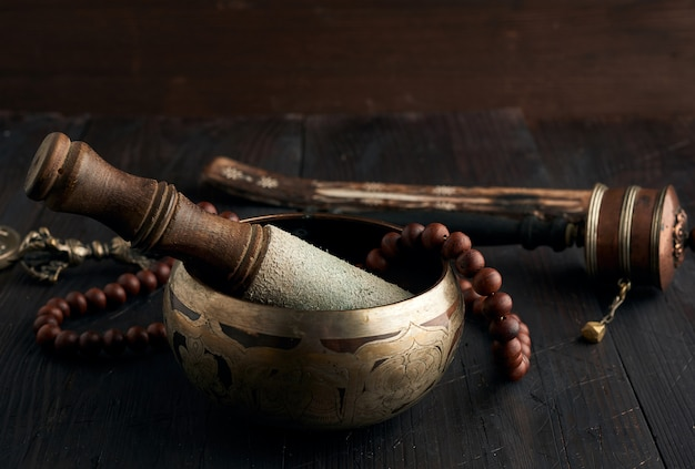 Tibetan singing copper bowl with a wooden clapper on a brown wooden table, objects for meditation and alternative medicine