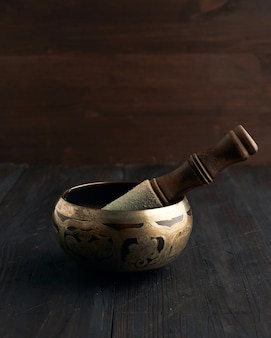 Tibetan singing copper bowl with a wooden clapper on a brown wooden table, objects for meditation