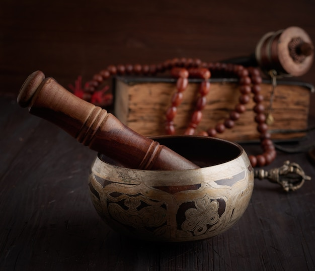 Tibetan singing copper bowl with a wooden clapper on a brown wooden table