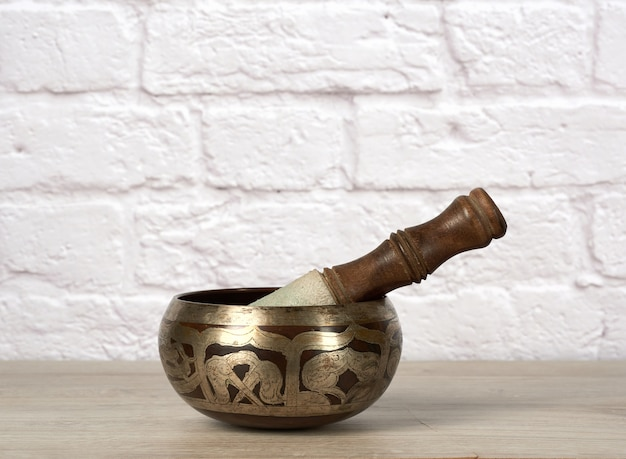 Tibetan singing copper bowl with a wooden clapper on brown wooden table