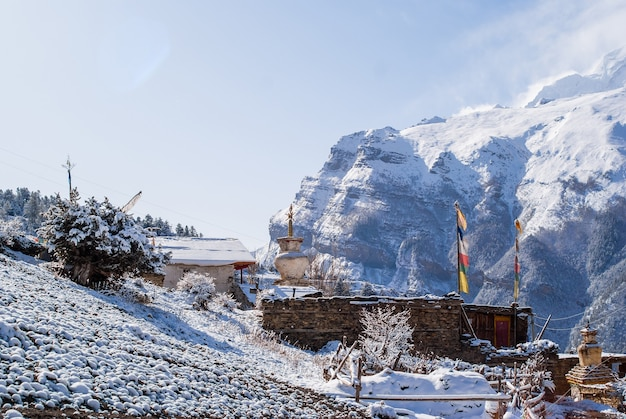 Tibetan village covered with snow in himalaya mountains with snowy peak