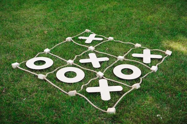 Крестики-нолики. игра на зеленой траве