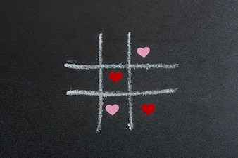 Tic tac toe game with little ornament hearts