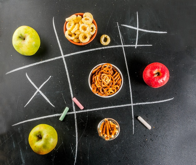 Tic tac toe healthy and unhealthy snack concept with crackers, chips and apples on black chalkboard