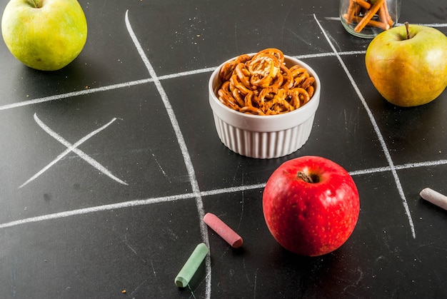 Tic tac toe healthy and unhealthy snack concept with crackers, chips and apples