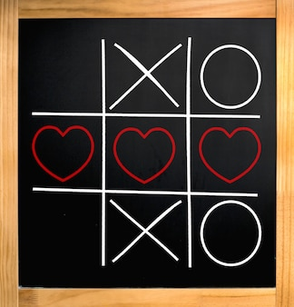 Tic tac toe hearts and xo over blackboard