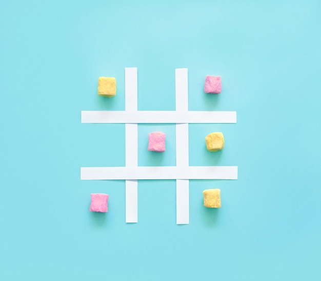 Tic tac toe made of pink and yellow marshmallows on a blue background.