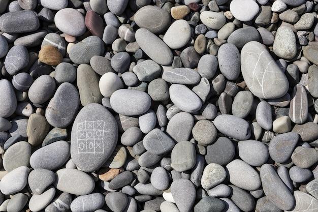 Крестики-нолики на берегу моря из гальки