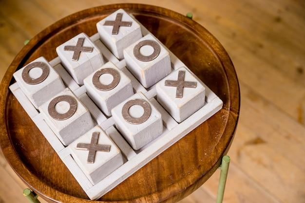 Деревянные tic tac toe ox игра. концепция стратегии, риск, конкуренция в бизнесе. винтажная печать x и o в деревянной гранжевой печатной машинке box.cross-zero. игра на деньги