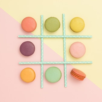 Tick-tack-toe made of macaroons and straws on pastel background. flat lay. healthy food concept.