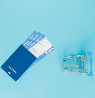 Tickets for airplanes and passport, and shopping cart on a blue surface. copy space for text.