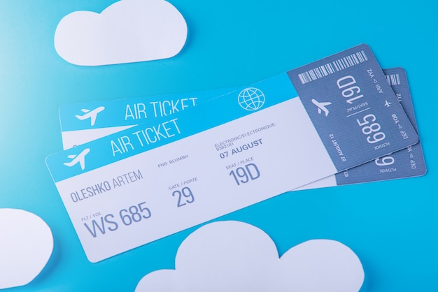 Билеты на самолет на голубом бумажном небе с облаками