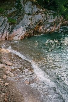 Приливная скважина, волна накатывает на пляж и зеленую скалистую гору поблизости