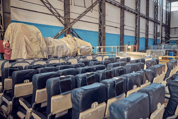 Tidies passenger seats waiting for cleaning duties in the aviation hangar