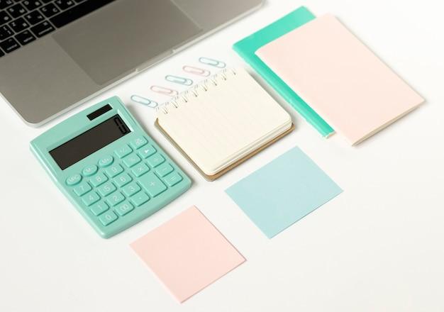 노트북, 펜, 메모장, 커피 한잔과 테이블에 누워있는 다채로운 스티커가있는 깔끔한 사무실 테이블