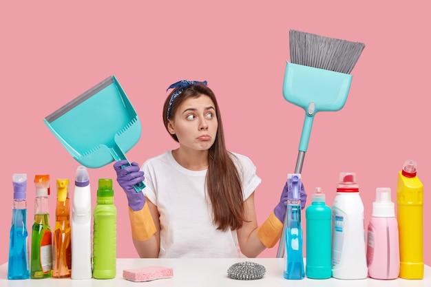 깔끔함과 청소 개념. 매력적인 검은 머리 여자는 머리띠를 쓰고, 화난 표정을 짓고, 빗자루와 국자를 들고, 혼자 집안 청소를합니다.
