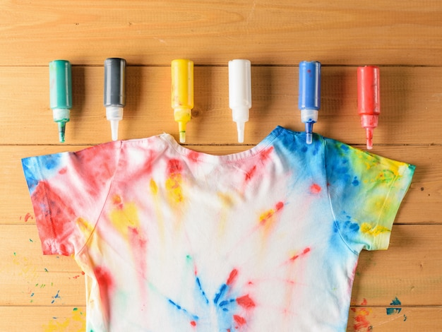Tie dye style t-shirt and six cans of fabric paint on wooden table.